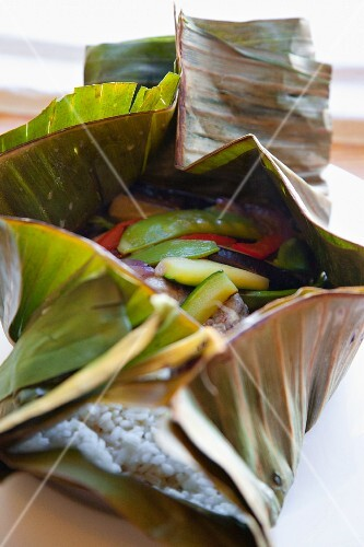 Rice, courgette, peas, peppers and onions in a banana leaf