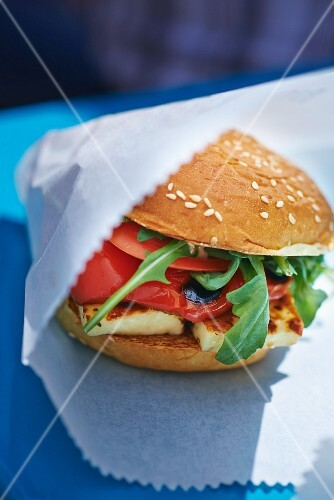 Veggie burger with halloumi in a paper bag