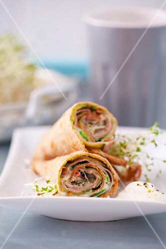 Tortilla wraps cut in half with Parma ham, cucumber, lambs lettuce, sprout and yoghurt dressing