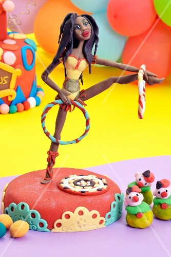 A party cake decorated with a circus artist figurine