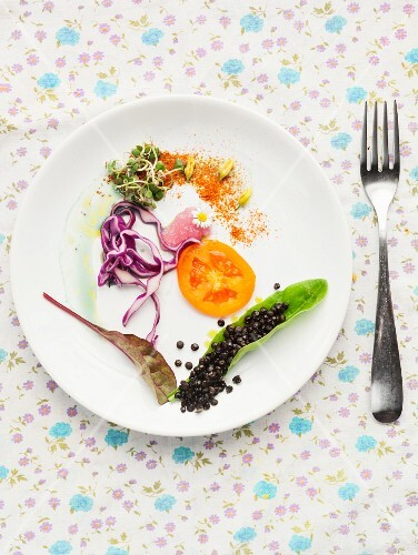 A salad plate with tomato, red cabbage, edible shoots and black lentils