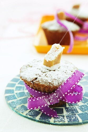 Hazelnut and toffee muffin with icing sugar, as a gift