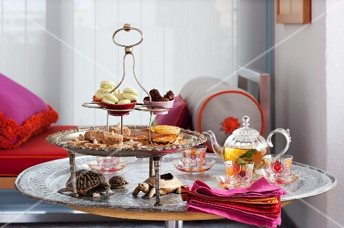 Tiered cake stand with assorted baked goods, a teapot and elegant glass teacups