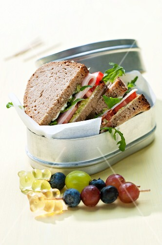 Wholemeal bread sandwiches filled with pesto, ham and tomato