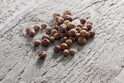 Allspice berries on grey wood