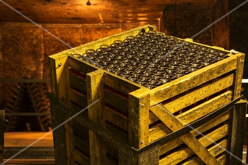 Fermentation according to the méthode champenoise in a wine vault; a wooden crate of bottles