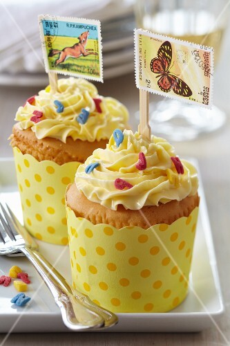 Cupcakes decorated with flags made from postage stamps