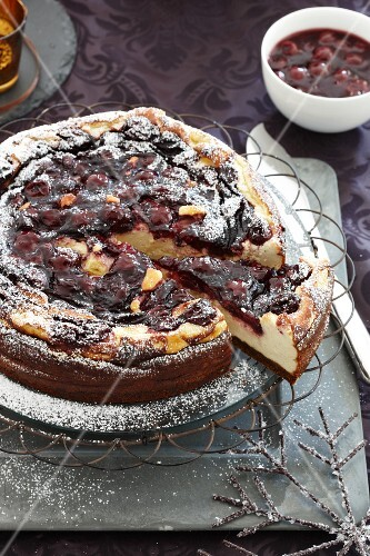 Baked cheesecake with mulled wine cherries, partly sliced, for Christmas