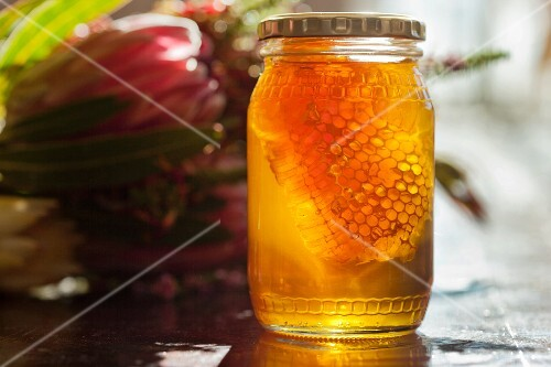 Honey with honeycomb in a screw-top jar