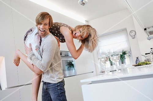A young man carrying his girlfriend over his shoulder through the kitchen
