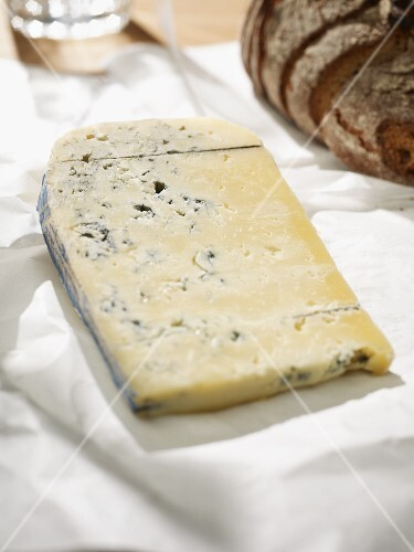 Blue cheese on white baking paper; in the background, rustic bread