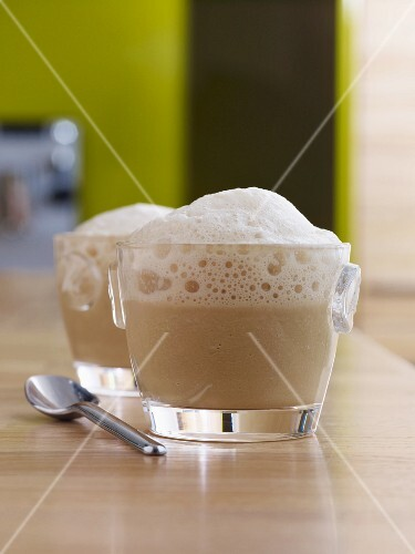 Two glass cups of cappuccino, topped with milk froth