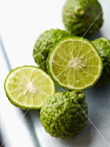 Whole and halved kaffir limes