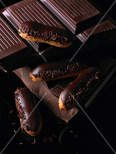 Chocolate éclairs on a stack of cooking chocolate