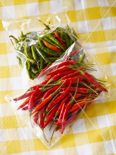 Fresh green and red chillies in bags