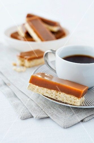 Shortbread topped with caramel, with a cup of coffee