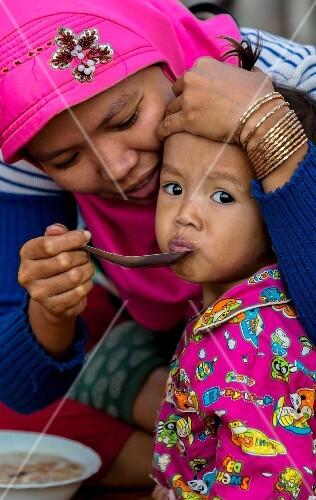 Woman feeding her child rice porridge, Kompong Cham, Cambodia