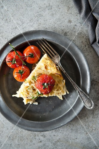 A slice of fennel gratin with cherry tomatoes on a plate (view from above)