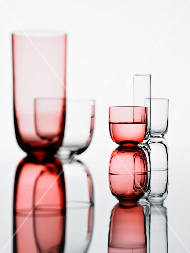 Two groups of glasses on a reflective white background
