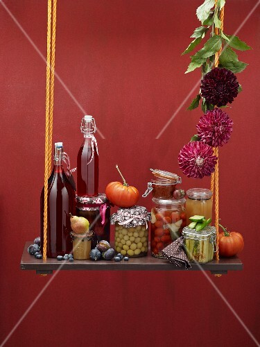 An autumnal still life featuring bottled vegetables and fruit