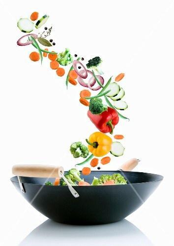 Vegetables falling into a wok