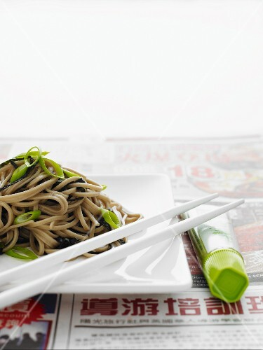 Japanese soba noodles on a white plate with white chopsticks