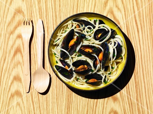 A bowl of cooked mussels with spaghetti