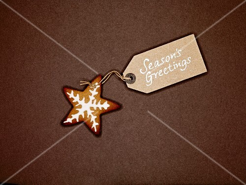 Star shaped ginger bread biscuit with white icing, and Christmas gift-tag, on a brown background