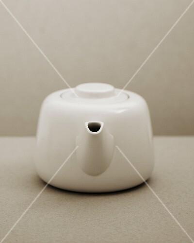 White teapot on a two-tone grey background