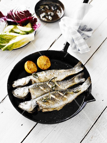 Three panfried whole bass, served in a cast-iron pan