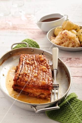 Knusprig gebratener Schweinebauch am Stück, im Hintergrund Sauerkraut und Kartoffelknödel