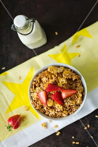 Granola with strawberries and a bottle of milk