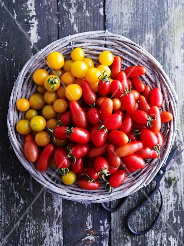 Various types of cocktail tomatoes in a basket (seen from above)