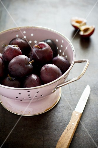 A colander of freshly washed plums