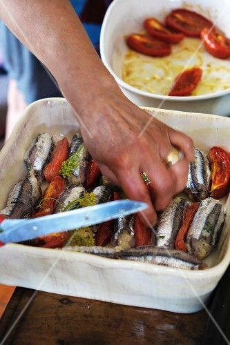 Bread-stuffed anchovies and tomatoes being placed in a dish