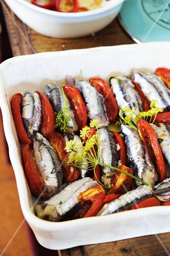 Bread-stuffed anchovies and tomatoes in a baking dish