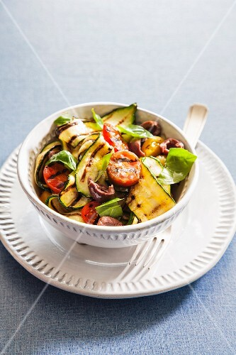 Grilled zucchini with tomatoes, olives and basil