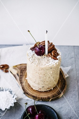 Pecan nut cake with cherries and a candle