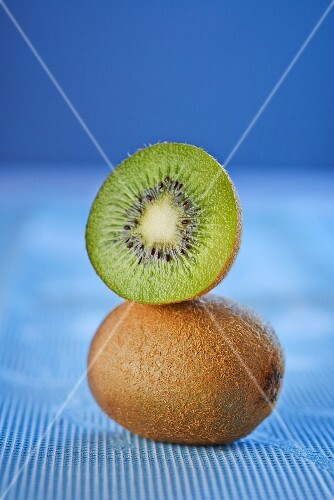 A whole and a half kiwi stacked on on top of the other