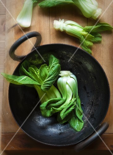 Baby Bok Choy in a Wok and on a Cutting Board