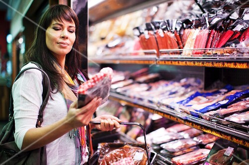 A young woman buying meat from the chiller aisle