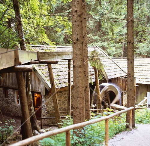 A historic mill building in the forest with a turning waterwheel - fairytale-like and secret