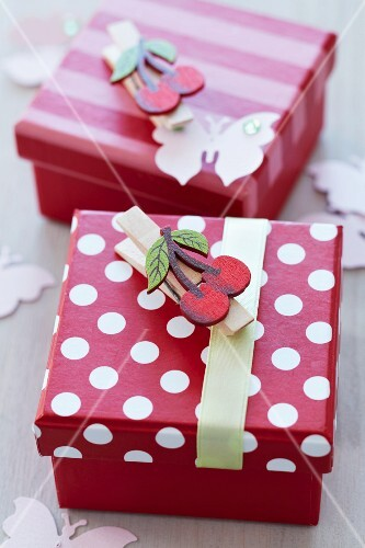 Pretty, red and white gift boxes decorated with clothes pegs with cherry motifs