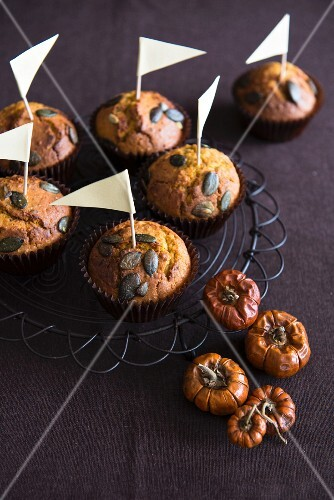Pumpkin muffins with pumpkins seeds and small flags