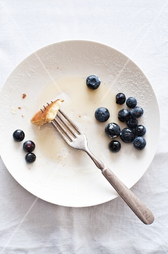 The remains of pancakes with blueberries and maple syrup on a plate with a fork