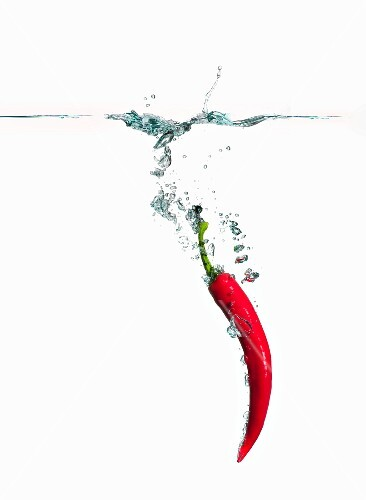 A red chilli pepper falling into water
