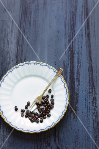 Coffee beans on a plate with a fork