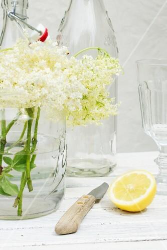 A still life featuring elderflowers, lemon, bottles and a knife