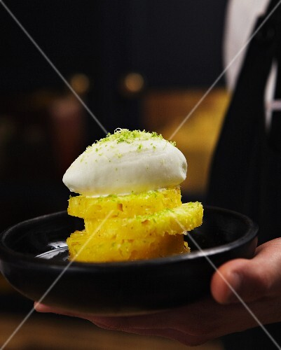 Pineapple slices topped with a dome of whipped cream and lime zest