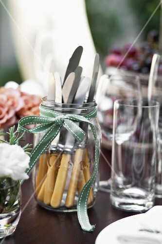 A decorated jar as a cutlery holder on a laid table